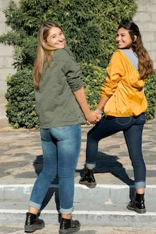 Two teenage girls holding each other's hand looking over shoulder at outdoors