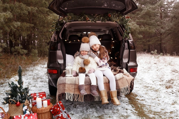 Two teenage girls hug in the trunk of a car decorated with christmas decorations