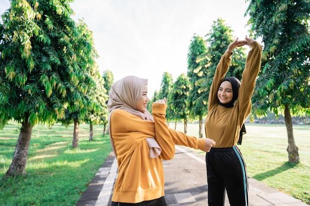 公園でのトレーニングの前に準備をしているときに手を伸ばすヘッドスカーフの2人の10代の少女