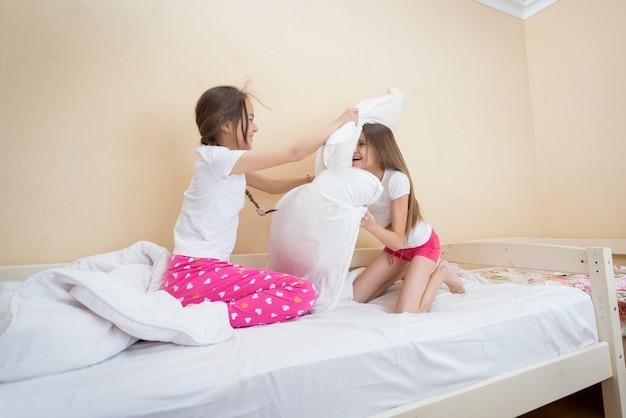 楽しんで枕と戦うパジャマ姿の2人の10代の少女