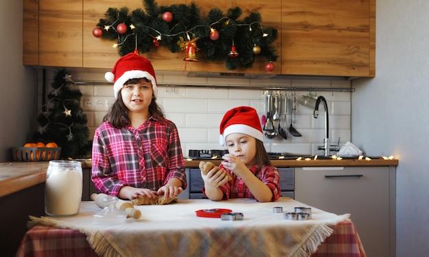 赤い格子縞のシャツとクリスマスの帽子をかぶった2人の10代の少女が、生地からジンジャークッキーを作り、陽気に笑っています。