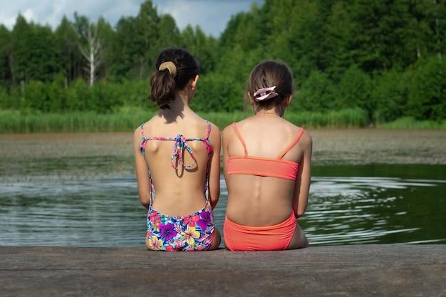 Две девочки-подростки в купальниках сидят на берегу озера после купания летом