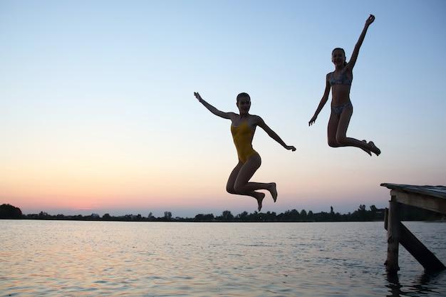 두 명의 십대 소녀가 저녁에 부두에서 물 속으로 뛰어듭니다.