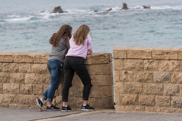 Two teenage girls looking at sea from retaining wall, old jaffa, tel aviv-yafo, israel