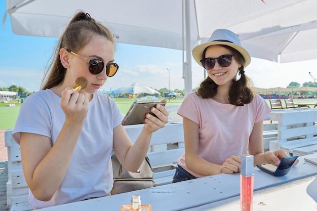 메이크업을 만드는 두 십 대 소녀, 여름 야외 카페에 앉아
