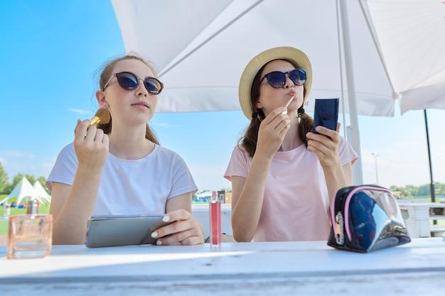夏の屋外カフェに座って、化粧をしている2人の10代の少女