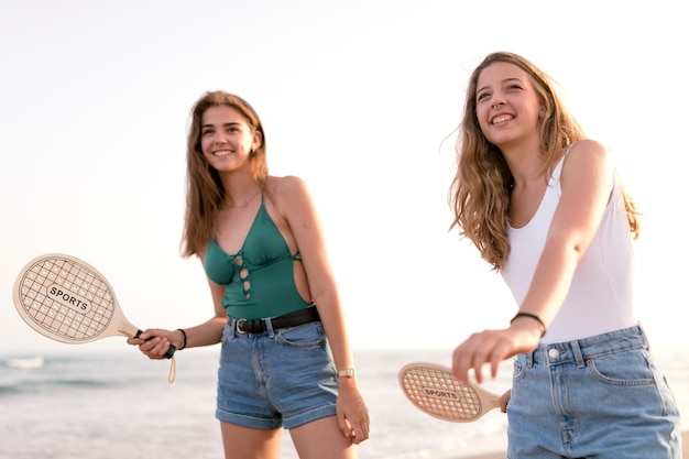 Two teenage girls playing tennis with racket at beach