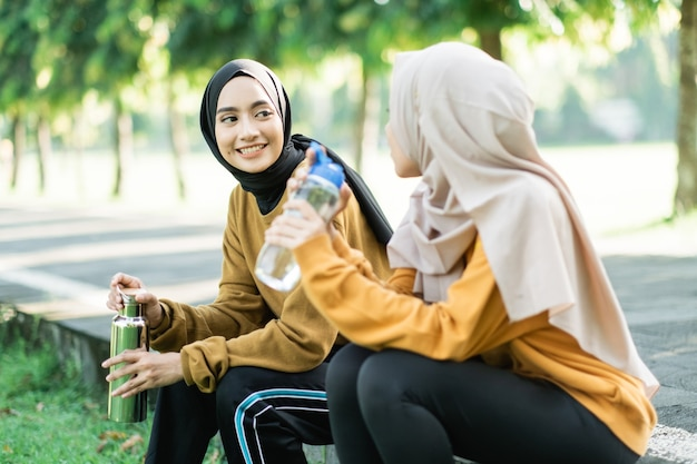Two teenage girls sitting enjoy drinking water with bottle after doing outdoor sports together the garden field