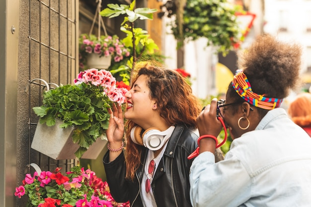 Two teenage girls smelling flowers