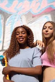 Две девочки-подростки вместе проводят время в парке на катке