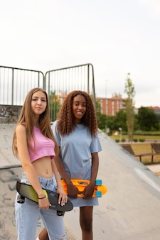Two teenage girls spending time together in the park at the skating rink