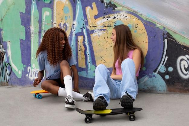 Due ragazze adolescenti trascorrono del tempo insieme alla pista di pattinaggio