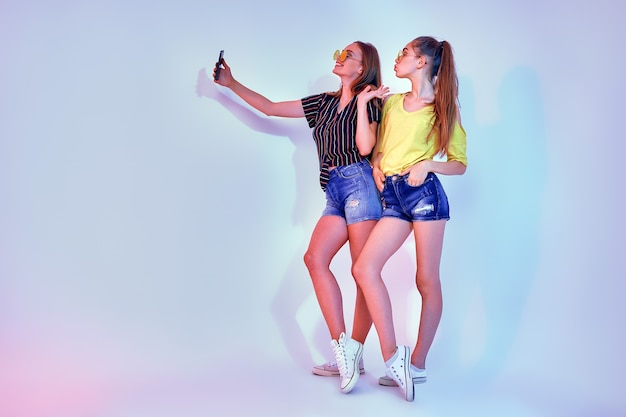 Two teenage girls in summer clothes standing in studio and making selfie on white background