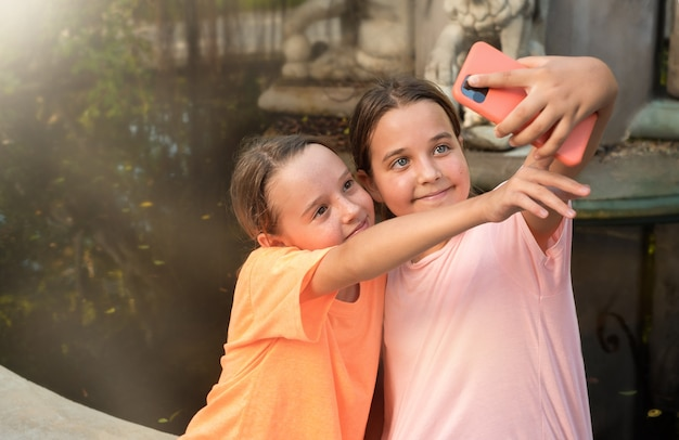 Two teenage girls taking selfie in the park near the fountain