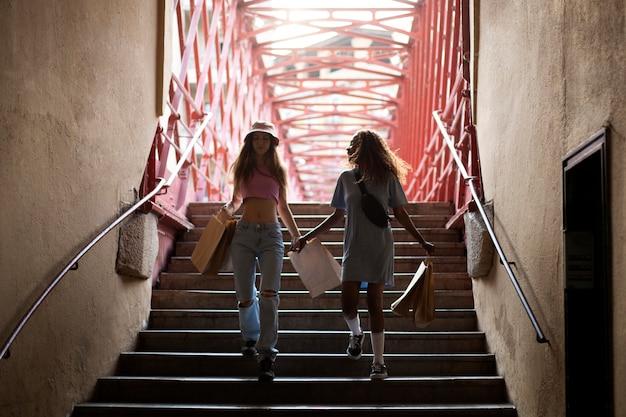 Due ragazze adolescenti che scendono le scale dopo aver fatto shopping e tenendo in mano le borse