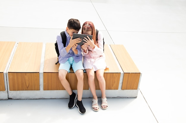 Two teenage schoolchildren playing tablet while sitting in the schoolyard, good mood, school time