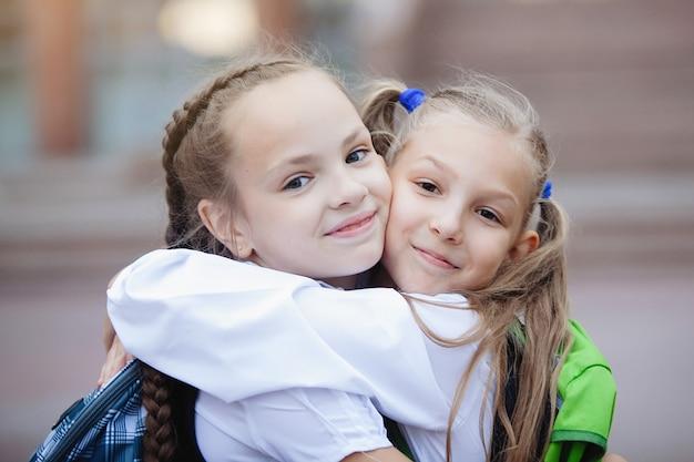 묶은 머리와 땋은 머리가있는 제복을 입은 두 십대 여학생이 포옹하고 기뻐하며 미소 짓습니다.