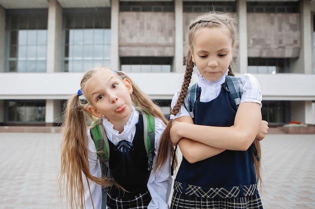 묶은 머리와 땋은 제복을 입은 두 십대 여학생이 카메라에 포즈와 얼굴을 찡 그리기.