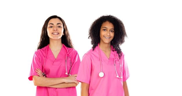 Двое студентов-врачей-подростков в розовой форме, изолированные на белом фоне