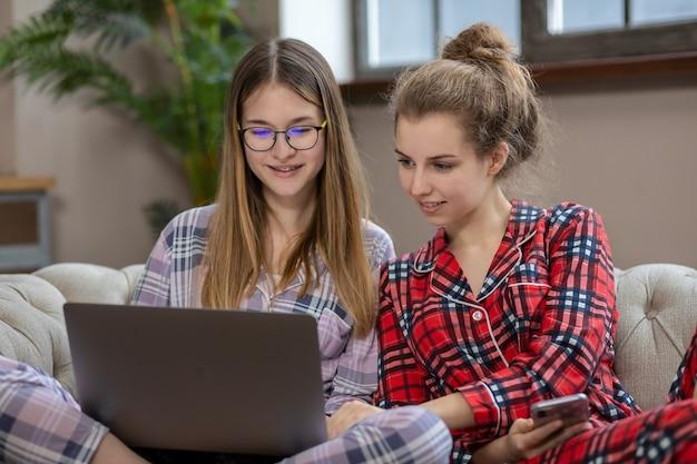 Две девочки-подростки в пижамах общаются в социальных сетях, сидя на диване дома