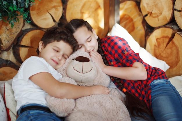 男の子と女の子の2人のティーンエイジャーがテディベアを抱いて横たわっています。子供の友情、コミュニケーションの喜び、幸せな子供時代。