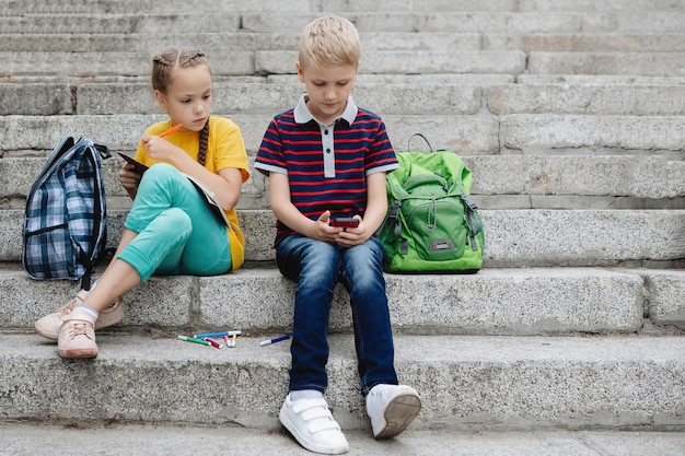 男の子と女の子の2人のティーンエイジャーがスマートフォンを手に階段に座っています。