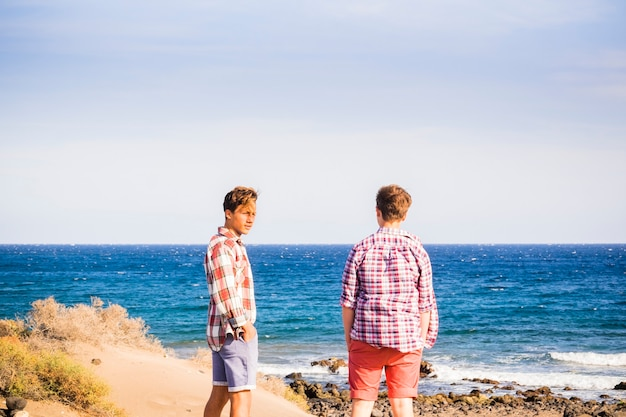 Two teenagers at the beach alones and isolated looking at the sea and talking together - adults front of the sea having fun and preparing to go surf