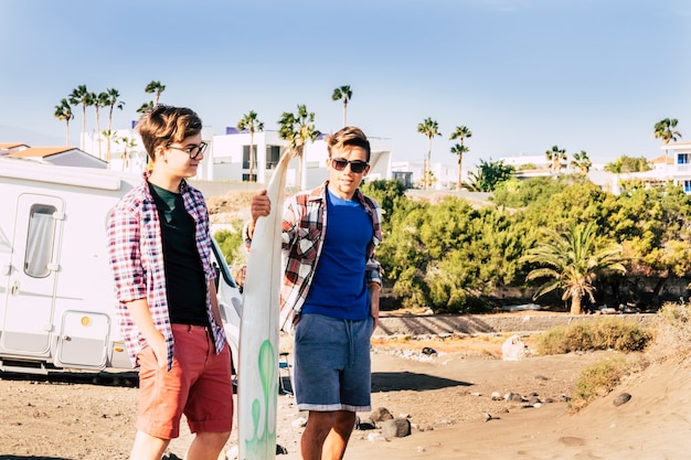 Two teenagers at the beach with one surfboard talking and looking at the sea and waiting to enter to the water to surf - vacations outdoors lifestyle