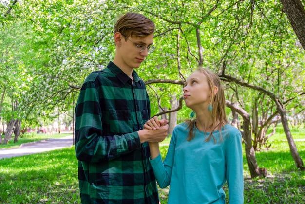 Два подростка, брат и сестра, общаются на открытом воздухе в парке