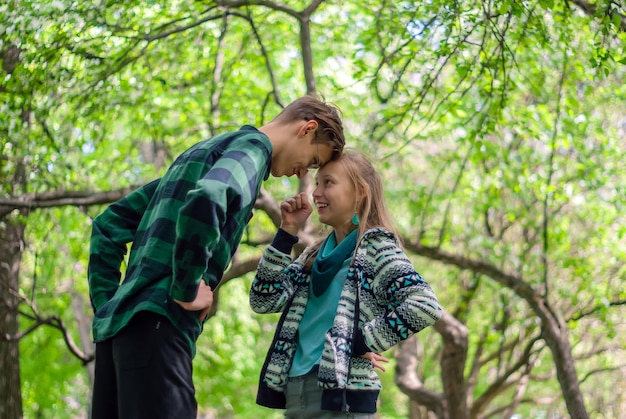 Два подростка общаются и спорят на открытом воздухе в парке