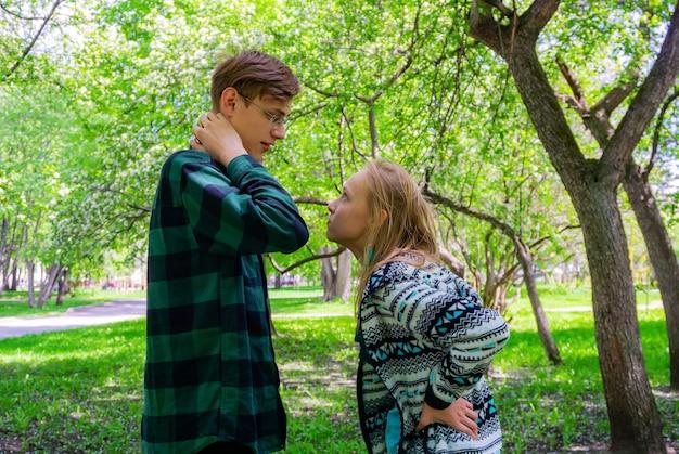 2人のティーンエイジャーが公園で屋外でコミュニケーションを取り、議論します