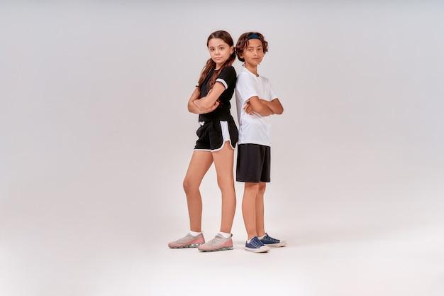 회색 위에 고립 된 포즈를 취하면서 카메라를보고 운동복에 두 십대 귀여운 소년과 소녀
