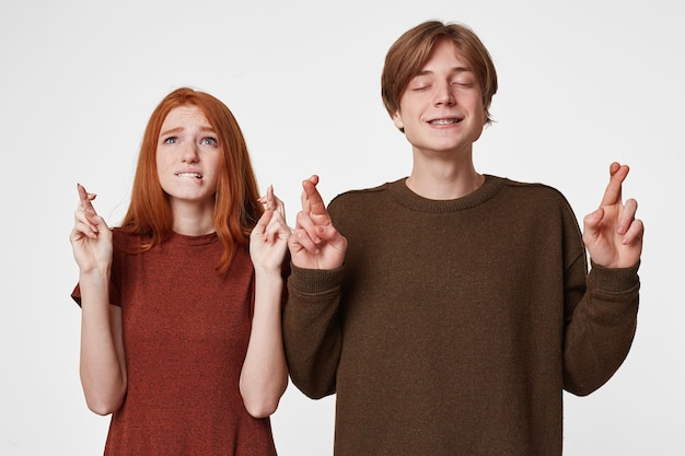 Two teenagers dressed casual keep heads and arms up and fingers crossed