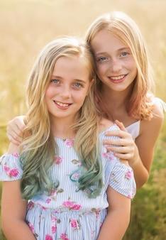 夏、暖かい日、色のついた髪のフィールドで、妹を抱き締める2人のティーンエイジャー Premium写真