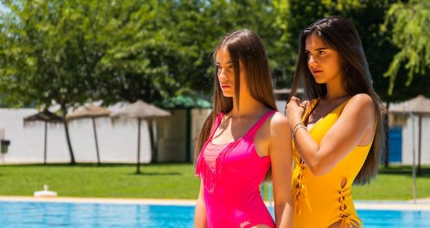 Двое подростков в купальниках в бассейне отеля позируют, копируют пространство