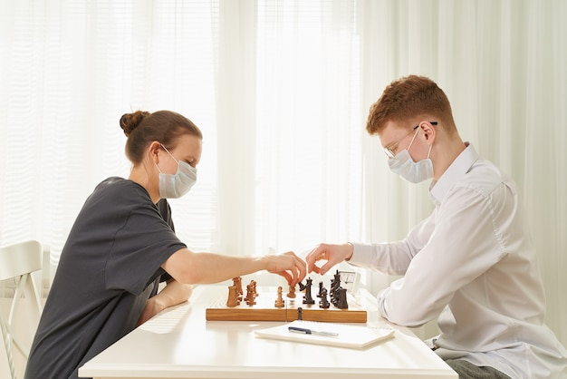 Two teenagers play chess during quarantine due to coronavirus pandemic