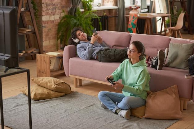 거실에 앉아서 함께 비디오 게임을 하는 두 십대