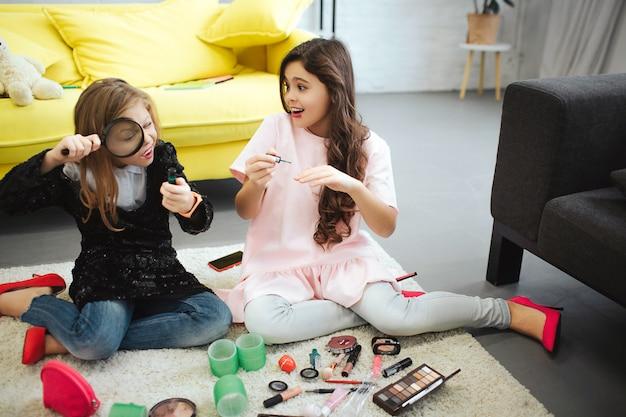 카펫 방에 함께 앉아 두 청소년입니다. 왼쪽에 소녀 루프를 통해 병을 봐. 그녀의 친구는 매니큐어를 넣었습니다. 그들은 바쁘다.