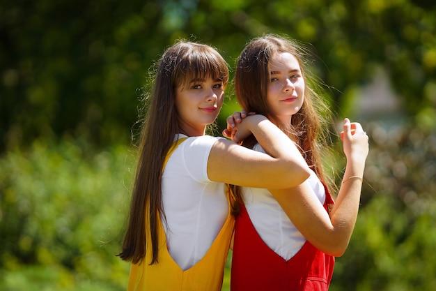 오후에 노란색과 빨간색 학교 드레스에 두 십대 쌍둥이
