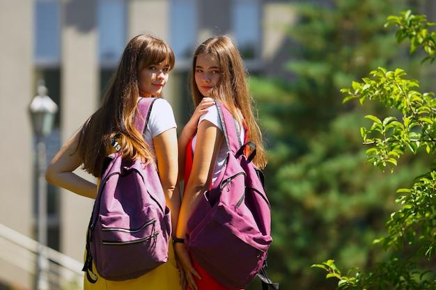 오후에 학교 밖에서 보라색 배낭과 노란색과 빨간색 학교 드레스에 두 십대 쌍둥이