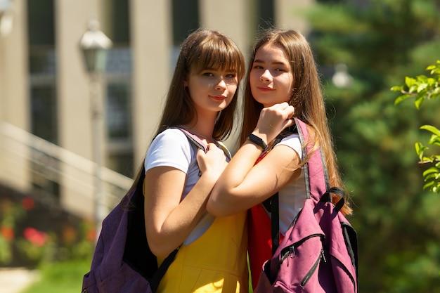 보라색 배낭과 노란색과 빨간색 학교 드레스에 두 십대 쌍둥이 학교에 걸어
