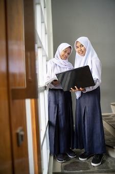 ノートパソコンを持って制服を着たスカーフを身に着けている2人のティーンエイジャー