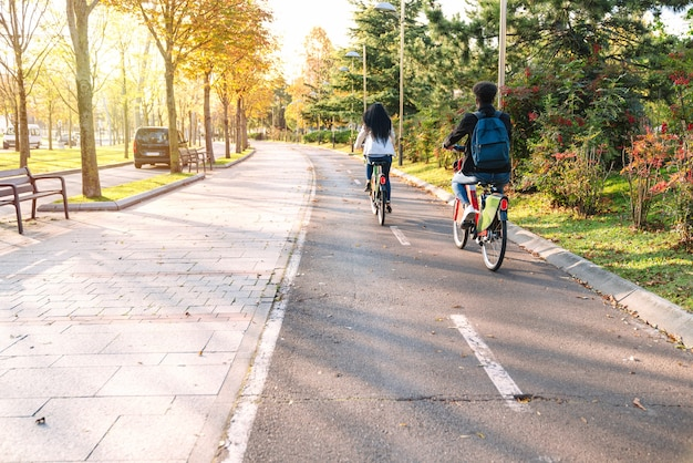 일몰에 많은 나무와 아름다운 공원에서 공유 전기 자전거 전자 자전거와 자전거 경로를 따라 타고 두 십대 젊은 학생 남자와 여자