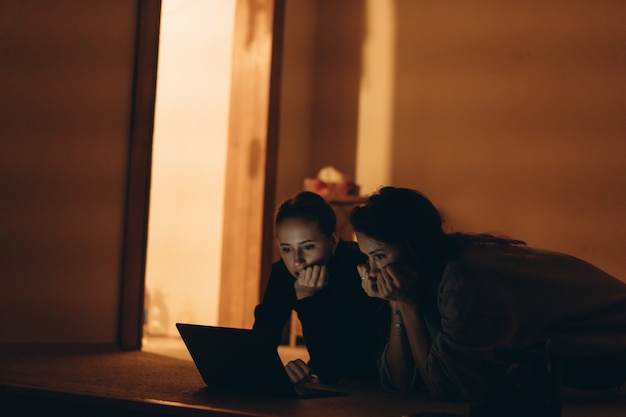 Two teens watching on line content in a laptop lying on the floor