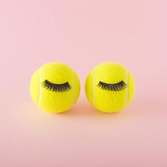ピンクの背景にまつ毛と2つのテニスボール。スポーツテニス競技シュールなコンセプト