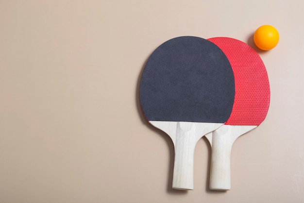 두 개의 테니스 라켓과 공은 베이지색 배경에 주황색과 흰색입니다. 스포츠 레크리에이션.핑퐁 라켓. 배너