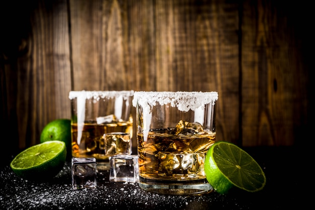 Two tequila shot glasses on dark table, with ice cubes, salt and limes