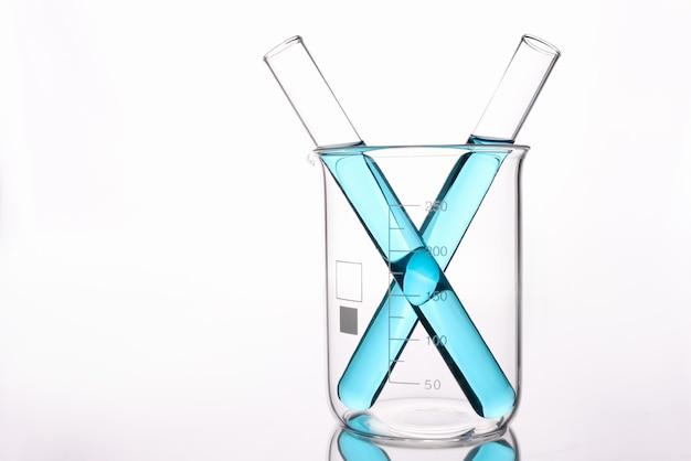 Две пробирки с синей кислотой, стоящие в стеклянном стакане на белой стене