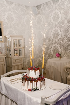 A two tier wedding white cake with years of raspberries and blackberries and a fountain of fireworks in the cake