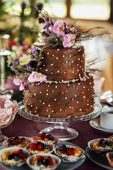 Two-tiered chocolate decorated with flowers cake on the holiday table